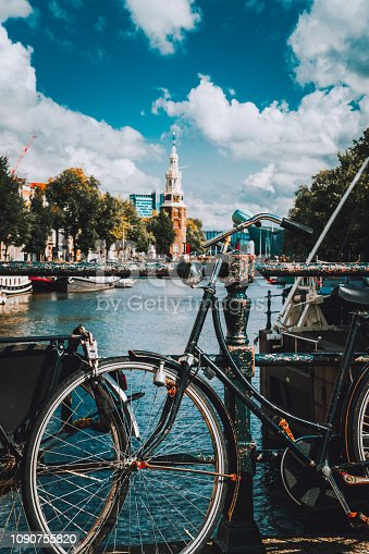 Close-up of Bike parked on a bridge in Amsterdam, Netherlands. Typical cityscape with Amstel river and motion clouds at the background.