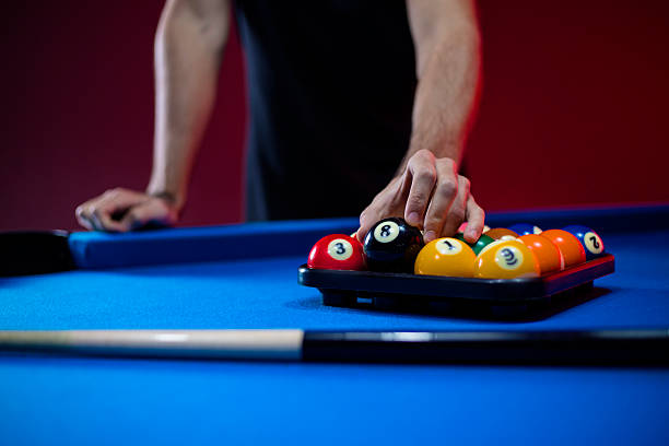 close-up of billiard balls on a blue pool table - pool cue stock photos and pictures