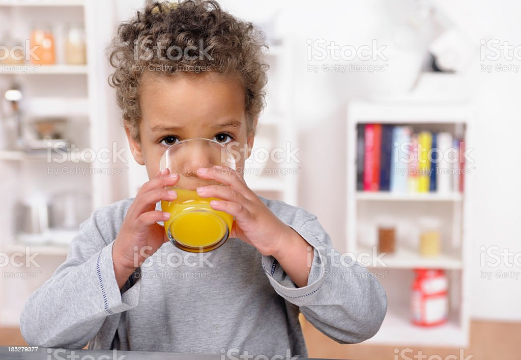 Close-up Of Biracial Toddler Drinking Orange Juice stock photo