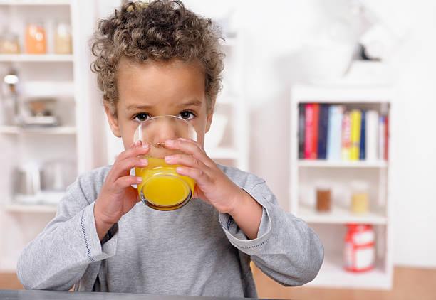 Nahaufnahme von Biracial Kleinkinder trinkt Orangensaft – Foto