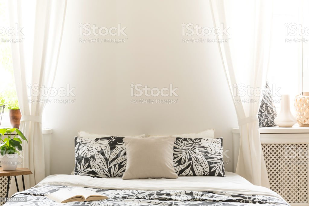 Closeup Of Black And White Flower Design Pillows On A Bed Lace Curtains On The Sides Of A Headboard In A Bright Bedroom Interior Copy Space Background Wall Real Photo Stock Photo