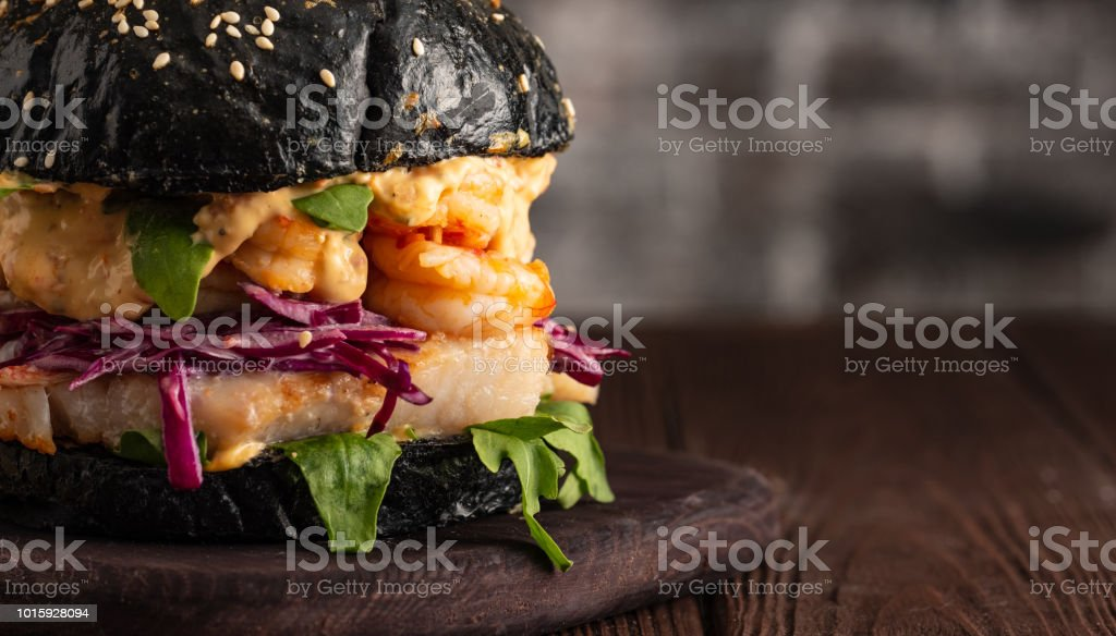 Closeup of  Black burger with fish and shrimps. Fishburger with prawns стоковое фото