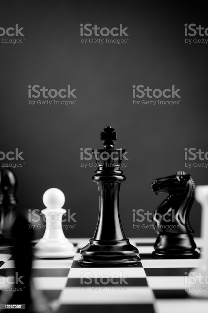 Close-up of Black Chess King among other figures on chessboard stock photo