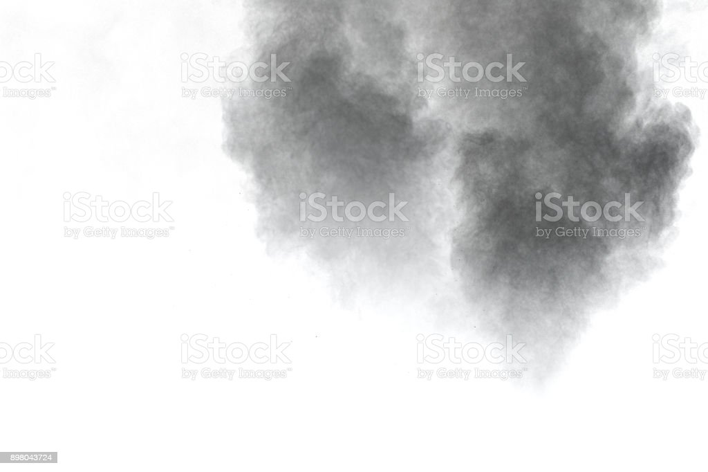 Closeup of black dust particles explosion isolated on white background. stock photo
