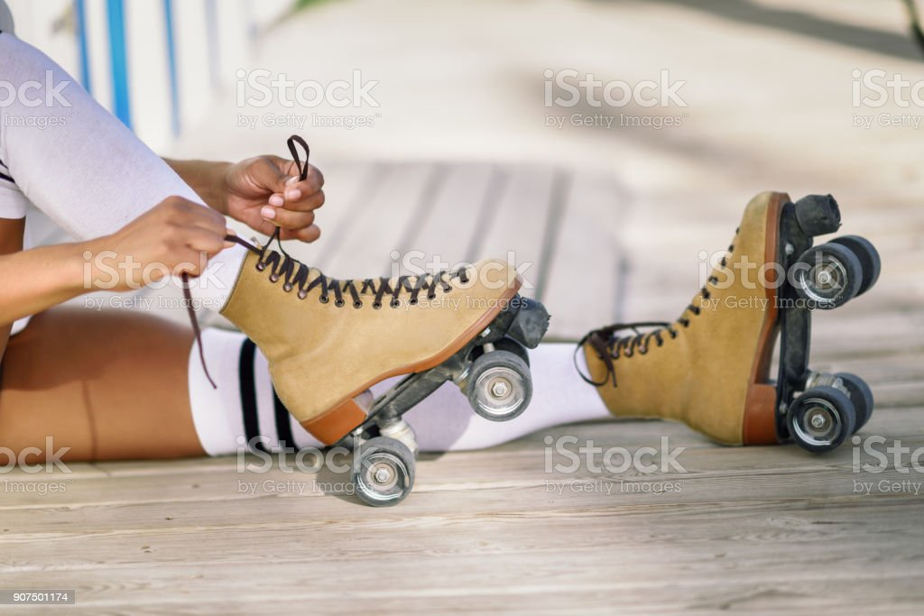 Close-up of black girl sitting on wooden floor puts on skates. stock photo