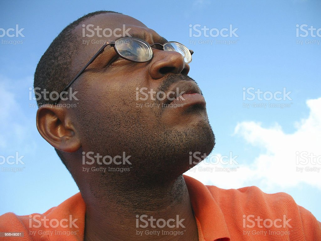 closeup of black man with eyeglasses looking to the sky royalty-free stock photo