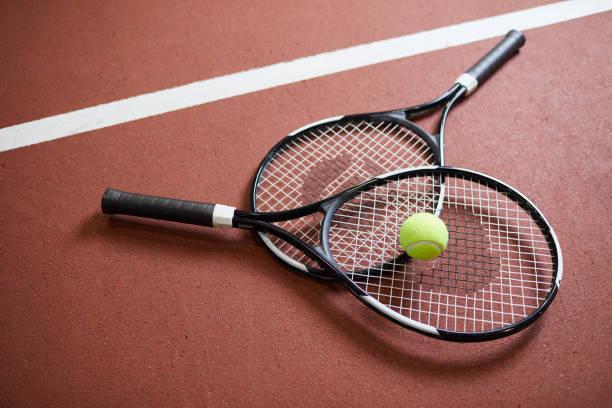 primer plano de las raquetas negras modernas con bola verde claro que se encuentra en el suelo de la cancha de tenis, deporte y concepto de hobby - tenis fotografías e imágenes de stock