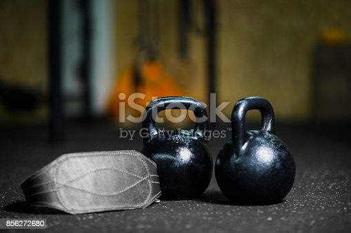 istock Closeup of black steel kettlebells used to perform ballistic exercises, gray athletic belt on a dark blurred background. 856272680