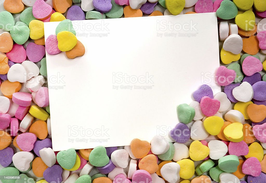 Close-up of blank white notecard surrounded by candy hearts stock photo