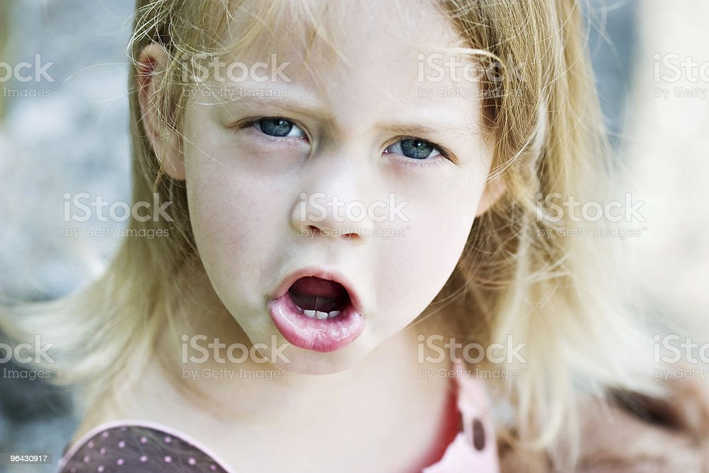 Close-up of blonde child's face with angry expression stock photo
