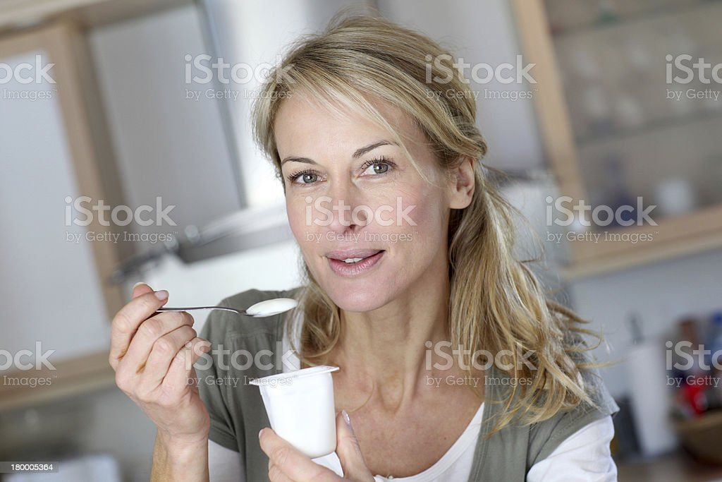 Closeup of blonde mature woman with yoghurt in hands stock photo