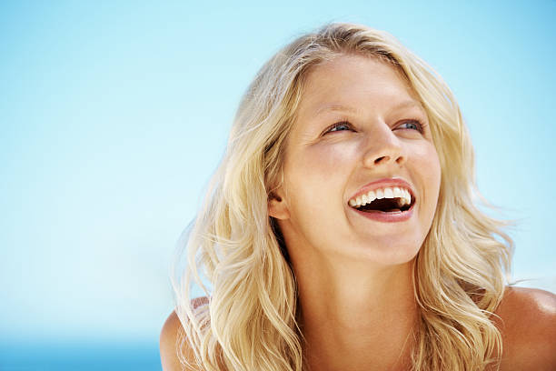 close-up of blonde woman looking at blue sky - medium length hair stock photos and pictures