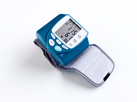 Close-up of blood pressure gauge for human wrist on white background.