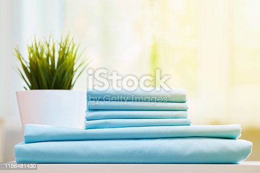 Closeup of blue clean bedding on a blurred background. A stack of folded new bed sheets on the table. Sunlight from the window.