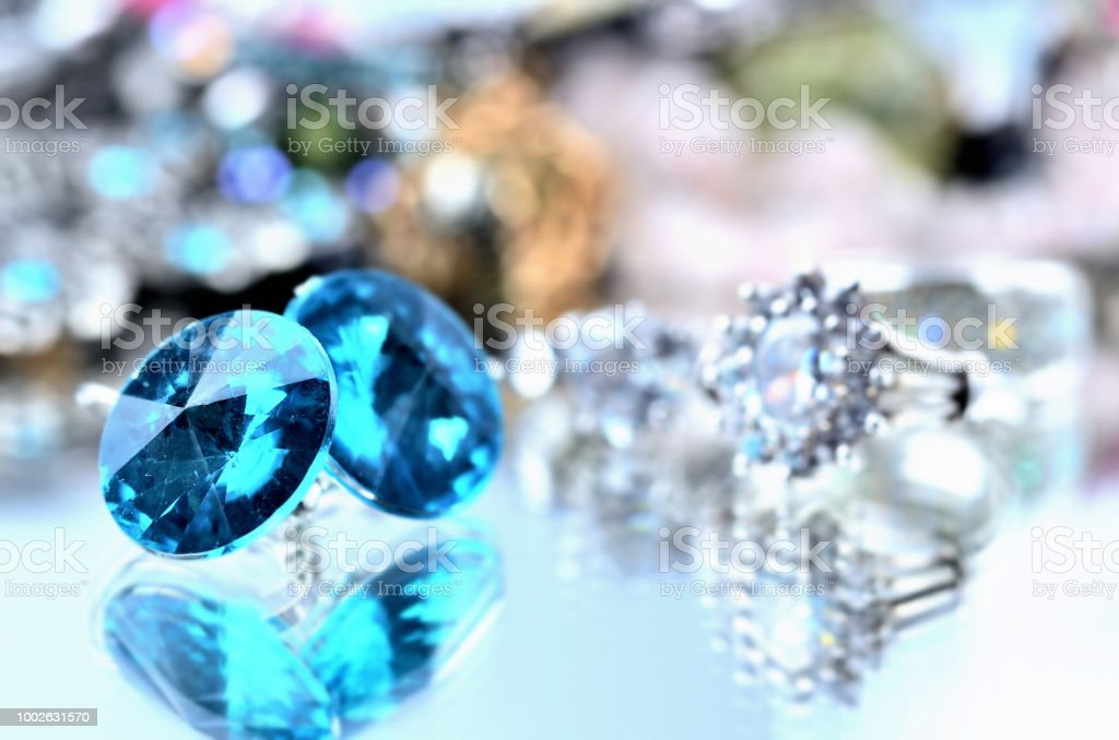 Close-up of blue earrings jewels - reflection effect - colored backgrounds with silver ring stock photo