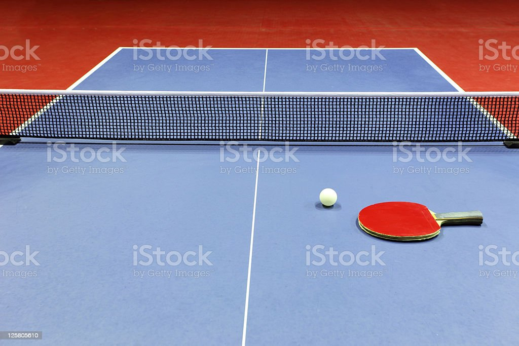 Close-up of blue ping pong table with red paddle on top stock photo
