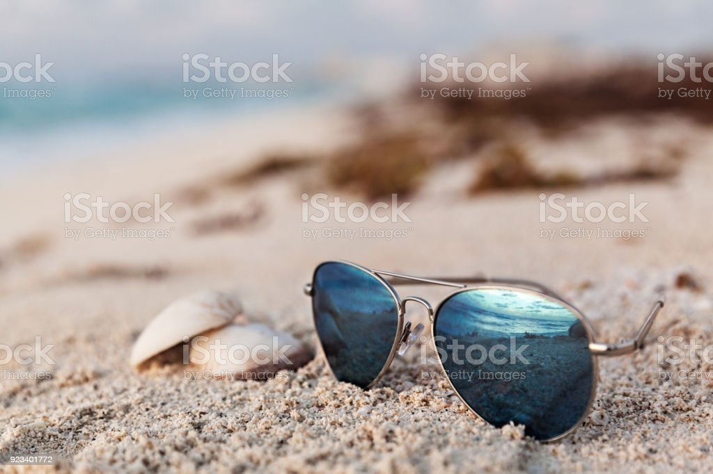 Closeup Of Blue Sunglasses On The Tropical Beach With Sand stock photo