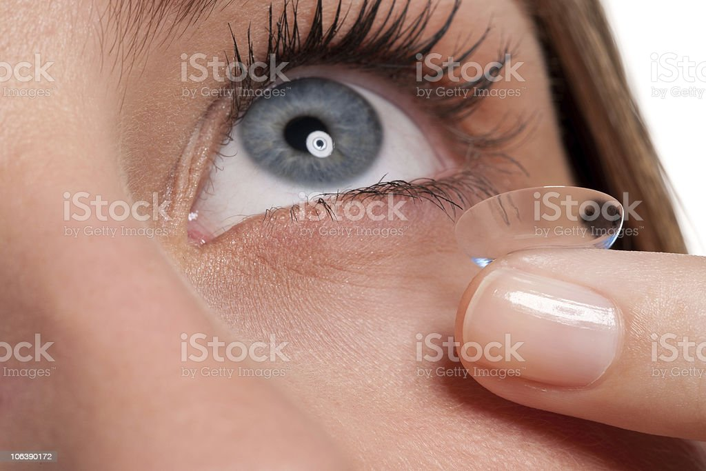 Close-up of blue woman eye with contact lens applying stock photo