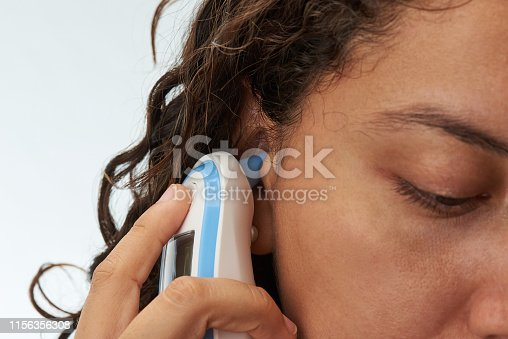 Close-up of digital body thermometer in woman ear