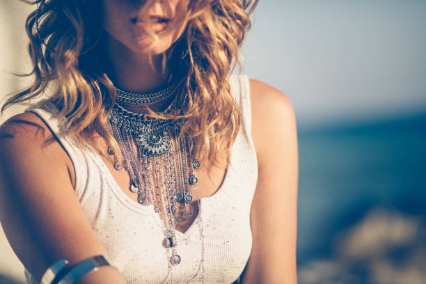 close-up of bohemian woman wearing silver fashionable jewelry - beach fashion stock photos and pictures