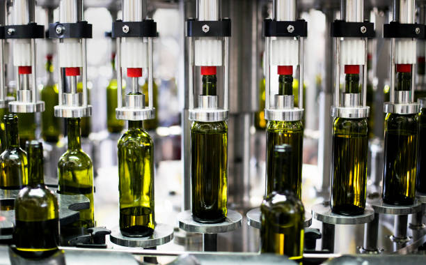 close-up of bottles in a bottling plant factory - bottling plant stock photos and pictures