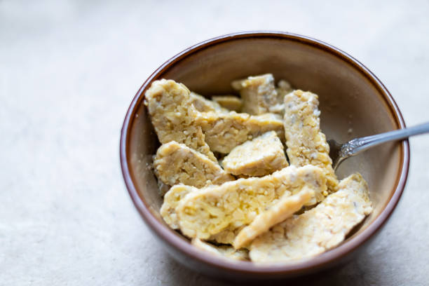 Closeup of bowl with sliced cut tempeh fermented soybeans on table cooking ingredient stock photo