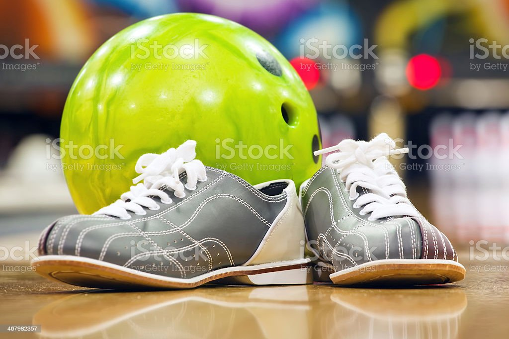 Close-up of bowling shoes and neon green ball stock photo