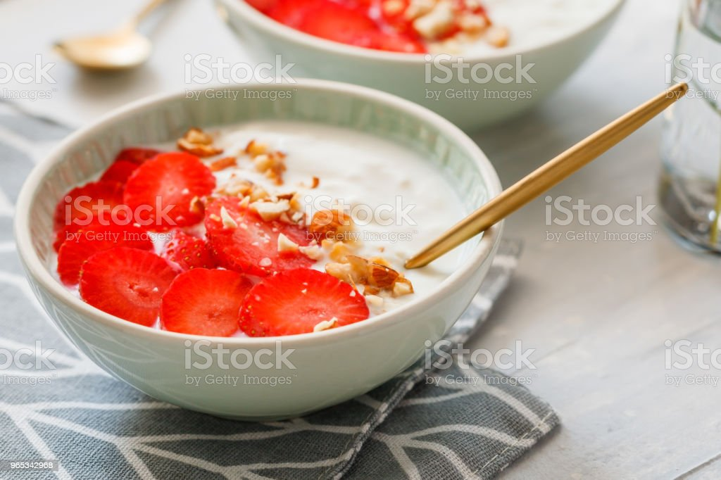 Close-up of bowls with coconut yoghurt, fresh strawberries and almonds. The concept of breakfast and a healthy lifestyle. Scandinavian style. royalty-free stock photo