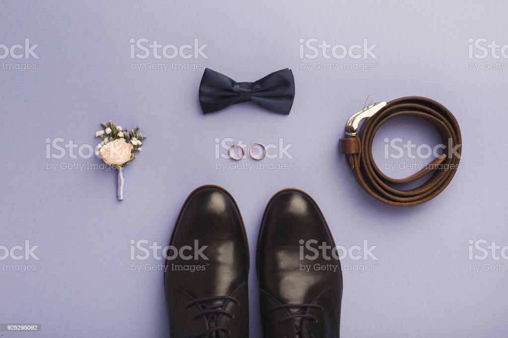 Closeup of bow-tie, belt, shoes, floral corsage, golden rings. stock photo