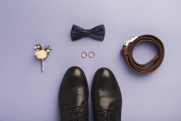 nahaufnahme der fliege, gürtel, schuhe, floral corsage, goldene ringe. - goldhochzeitsschuhe stock-fotos und bilder