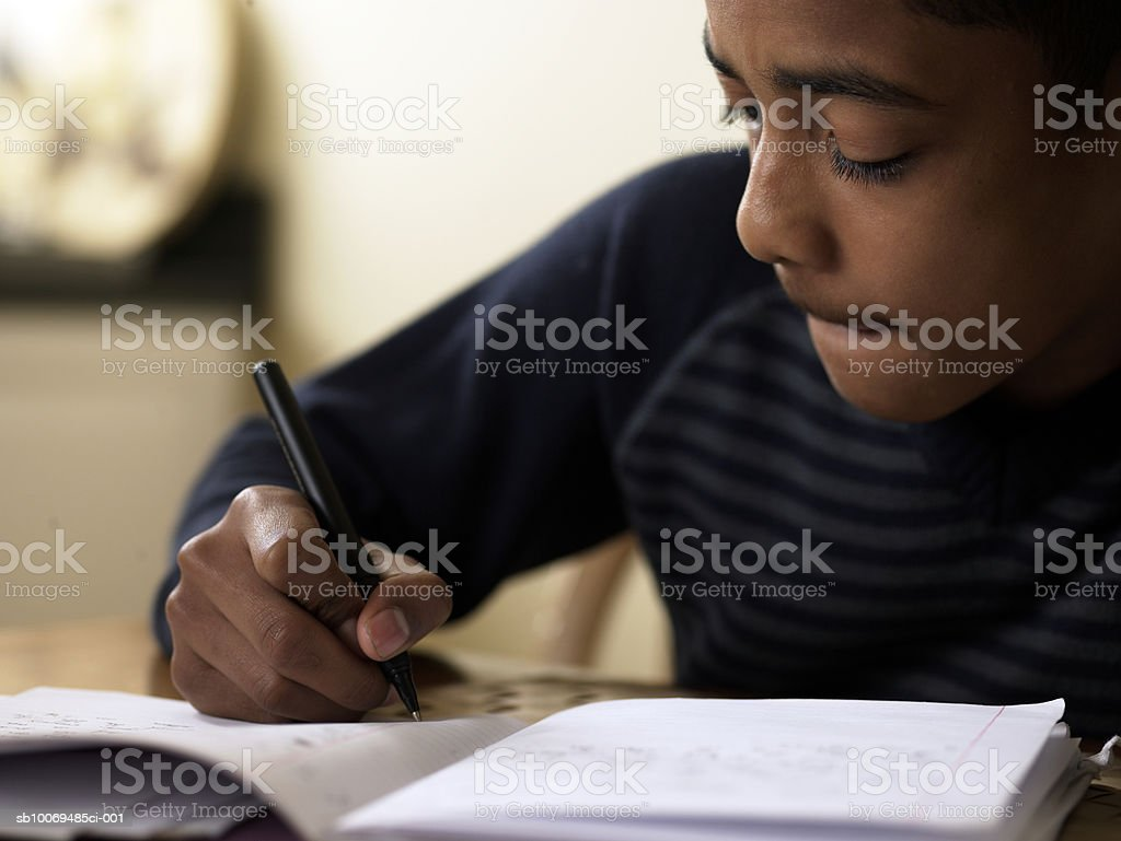 Close-up of boy (12-13) doing homework at desk 免版稅 stock photo