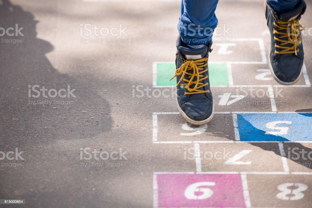 Closeup de pernas do garoto e amarelinha desenhada no asfalto. Criança brincando de amarelinha no playground ao ar livre em um dia ensolarado. actividades ao ar livre para crianças. - foto de acervo