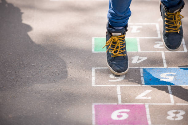closeup of boy's legs and hopscotch drawn on asphalt. child playing hopscotch on playground outdoors on a sunny day. outdoor activities for children. - plac zabaw zdjęcia i obrazy z banku zdjęć