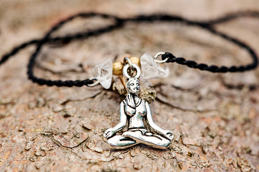 Closeup of bracelet with yoga girl in lotus position