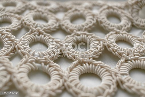 istock Close-up of braided cord pattern rings on white textured background. 627351768