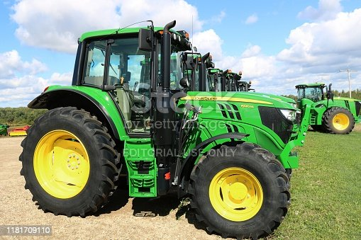 Walkerton, Ontario / Canada - September 24, 2019: Row of green and yellow John Deere tractors for sale lined up at Huron Tractor