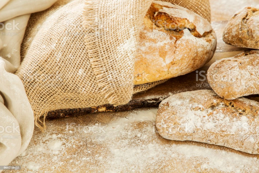 Close-up of bread and buns lying on a wooden table with flour on it in a bakery royalty-free stock photo