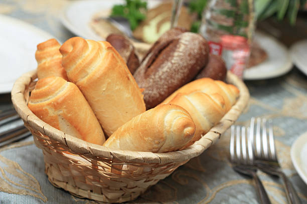 Closeup of bread rolls in basket on restaurant table stock photo