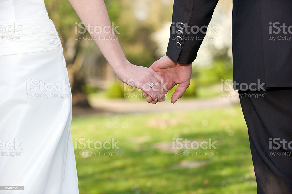 Close-up of bride and groom holding hands as newlyweds stock photo