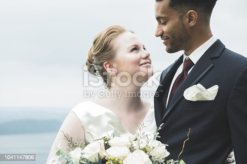 In this closeup, a beautiful bride stands outdoors with her groom and smiles up at him.  He looks down and smiles at her.  There is a scenic background.