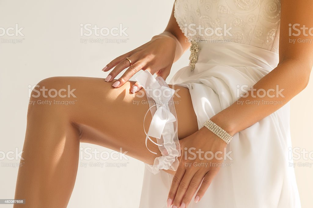 Close-up of bride's hands putting garter stock photo