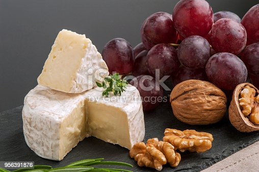 Close-up of brie cheese, herbs, nuts and red grape on black stone plate.