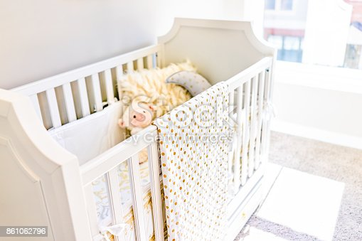 istock Closeup of bright yellow baby crib in nursery room with toys and pillow in model staging home, apartment or house 861062796