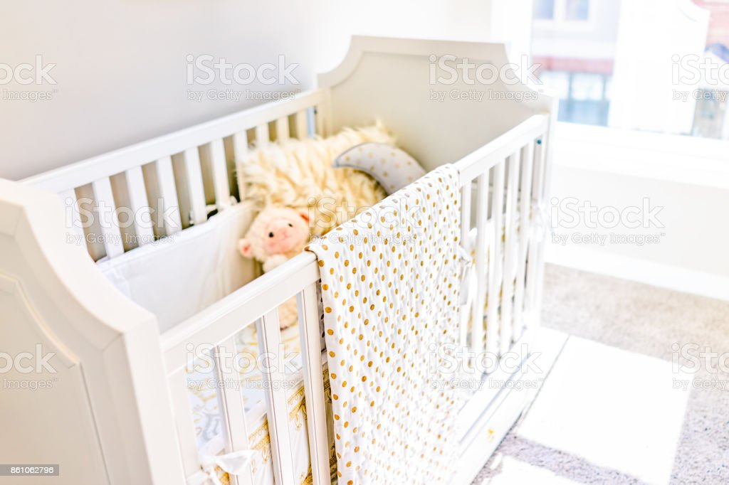 Closeup of bright yellow baby crib in nursery room with toys and pillow in model staging home, apartment or house stock photo