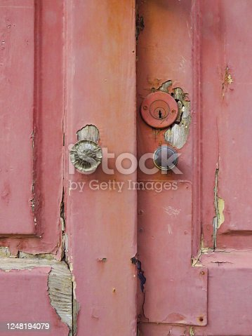 924754302 istock photo Close-up of broken and uncorked pink wooden door entrance with round door knobs. Old pink door with rusty and spoiled paint. 1248194079