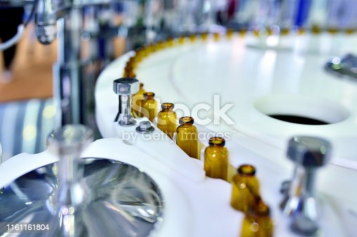 Close-up of brown glass bottle at turntable production line.