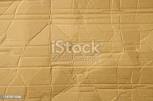 Overhead shot and close-up of brown wrinkled corrugated cardboard texture background.