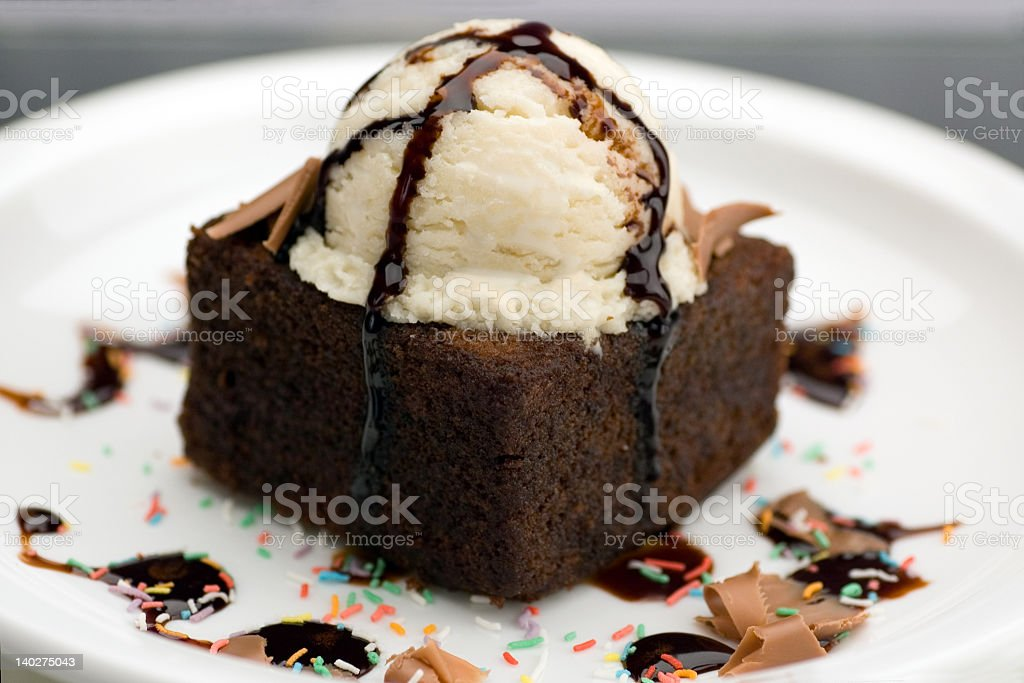 Close-up of brownie a la mode with chocolate syrup drizzles stock photo