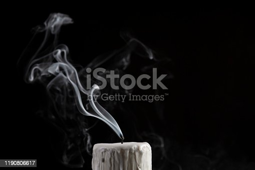 Smoke emitting from burnout candle against black background.