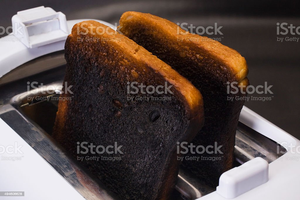 Close-up of burnt toasts in a toaster stock photo